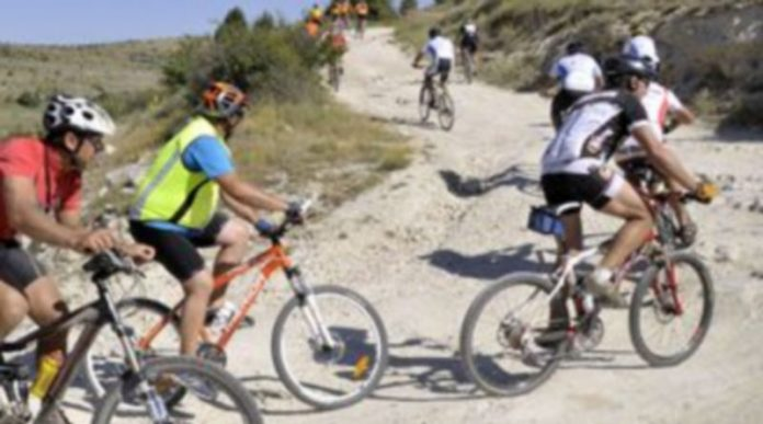 Un grupo de ciclistas ascienden por un camino de tierra con sus bicicletas de montaña. / Juan Martín