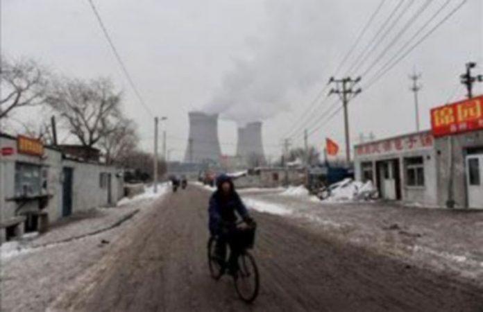 Un hombre conduce su bicicleta frente a una central eléctrica en Shenyang