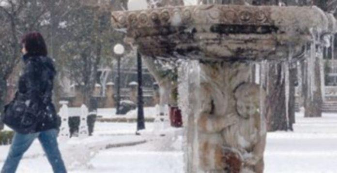 El agua de una fuente helada y una joven paseando por un parque de la ciudad de Soria con una importante capa de nieve. / Ical