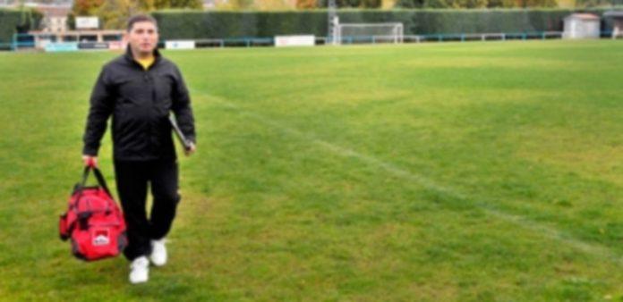 El entrenador Javier Jadraque camina por el césped del campo granjeño de El Hospital con una bolsa de deporte y una carpeta. / Kamarero