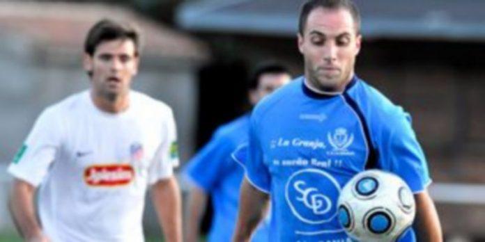 El jugador granjeño Iván observa el balón durante un encuentro en el campo de El Hospital. /Kamarero