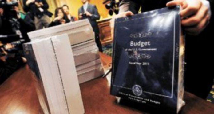Un trabajador del Senado de EEUU coloca sobre una mesa varios ejemplares del presupuesto público para el ejercicio fiscal 2011. / Reuters