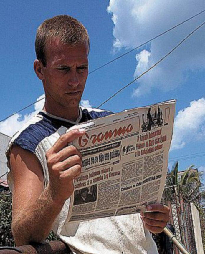 Un cubano lee las reflexiones de Fidel Castro en el diario oficial 'Granma'. / EFE)