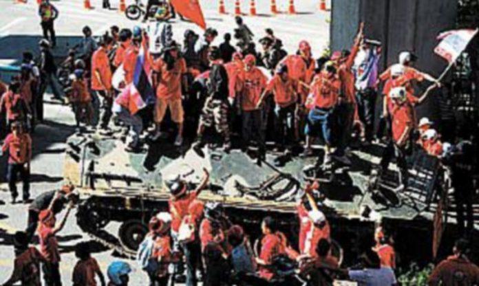 Los manifestantes se hicieron con el control de dos tanquetas militares que estaban apostadas frente a un centro comercial de la capital tailandesa. / EFE