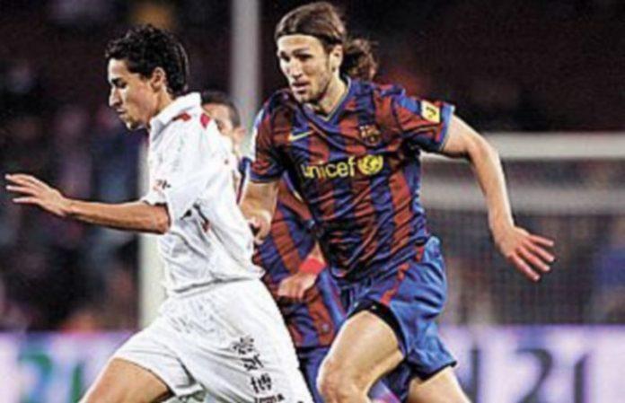 El barcelonista Chigrinsky intenta detener el avance del jugador del Sevilla Jesús Navas. / EFE