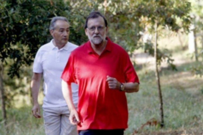 Mariano Rajoy acompañado por el marido de la presidenta del Congreso