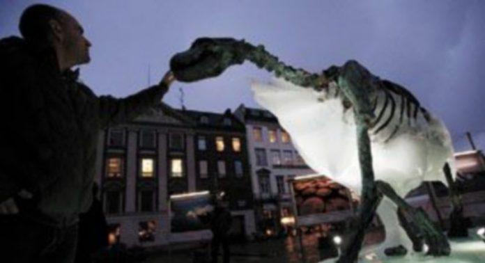Un hombre toca la escultura de hielo de un oso polar en Copenhague