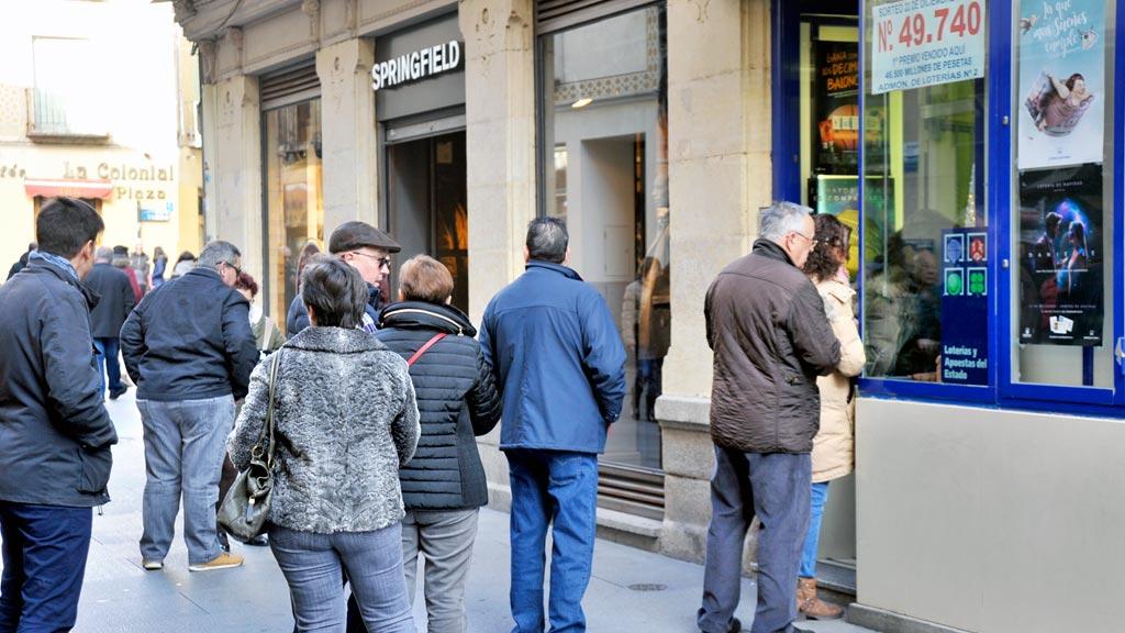 Segovianos y turistas hacen cola estos días en las administraciones segovianas, como ésta de la Calle Real, para comprar los décimos de la suerte. /kamarero