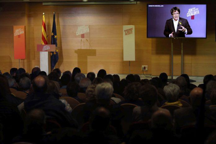 El expresidente Carles Puigdemont interviene por videoconferencia desde Bruselas durante el mitin.