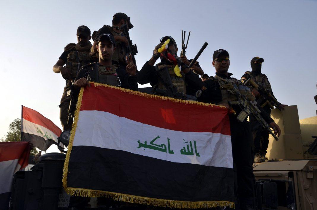 Imagen de archivo de varios combatientes de las tropas de Irak, sujetando una bandera de su país. /EFE