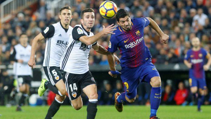 Luis Suárez y Gayá luchan por el balón durante el partido de Liga de esta temporada entre Valencia y Barça. / EFE