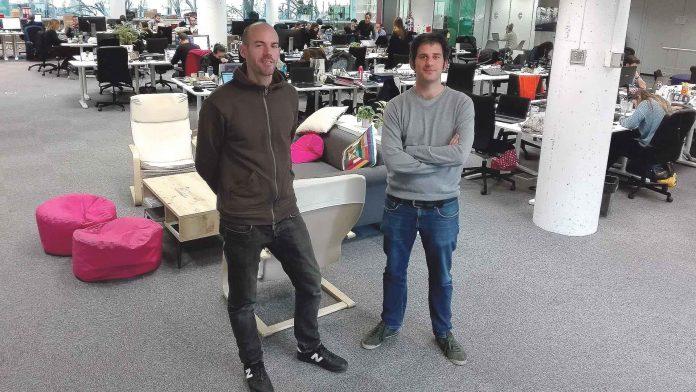 Los dos jóvenes emprendedores segovianos, en las oficinas centrales de Madrid, con parte de la plantilla de la empresa al fondo. / Florentino Descalzo.