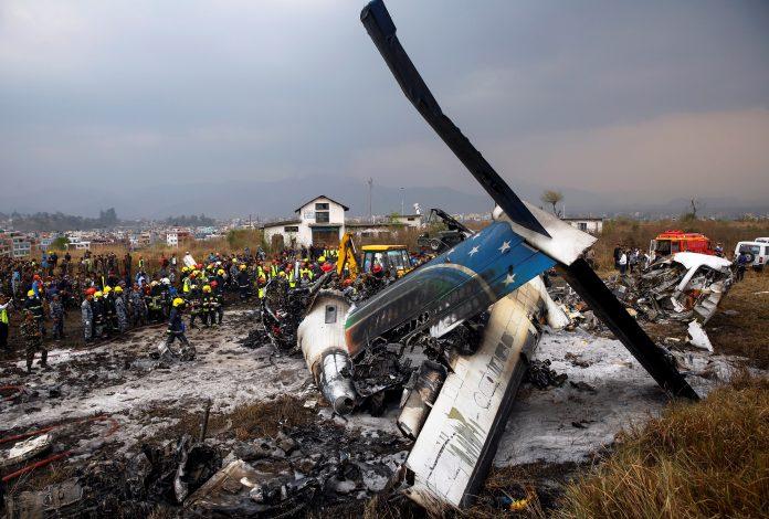 Los equipos de rescate trabajan entre los restos del avión que se estrelló en el aeropuerto de Katmandú.