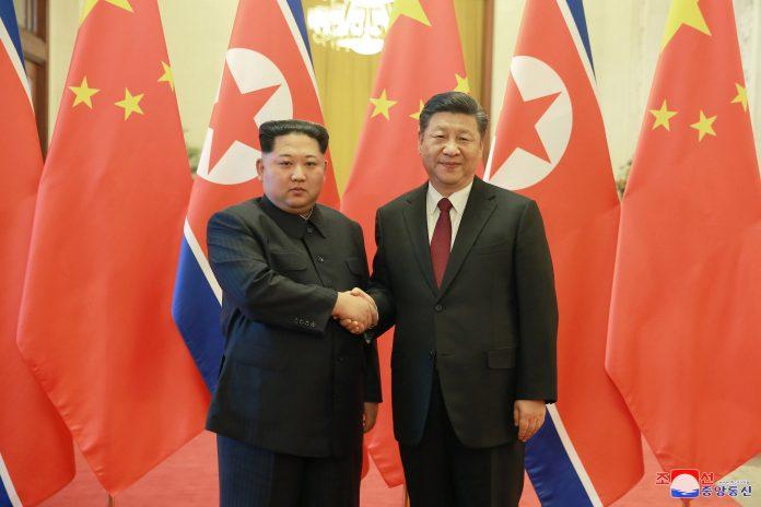 El líder norcoreano, Kim Jong-un (i), y el presidente chino, Xi Jinping posan ante los medios de comunicación.