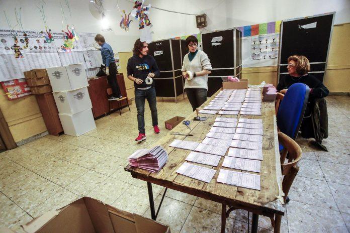 Varias personas preparan una mesa de votación para las elecciones que se celebrarán hoy en Italia. / EFE