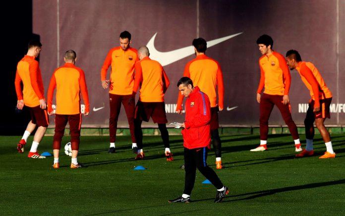 El técnico del FC Barcelona, Ernesto Valverde, pasa ante sus jugadores durante el entrenamiento de la plantilla.