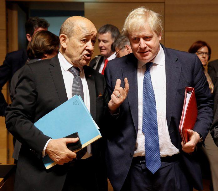 El ministro de Asuntos Exteriores francés, Jean-Yves Le Drian (i), conversa con su homólogo británico, Boris Johnson.
