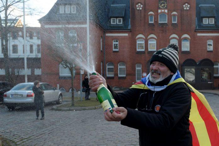 Un hombre con una estelada celebra con champán frente la cárcel de Neumünster la liberación de Puigdemont.