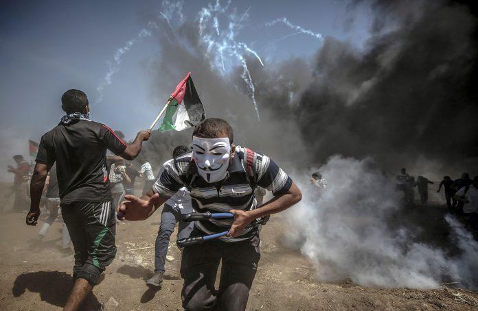 Manifestantes corren para protegerse del gas lacrimógeno lanzado por soldados israelíes en la frontera de Gaza.