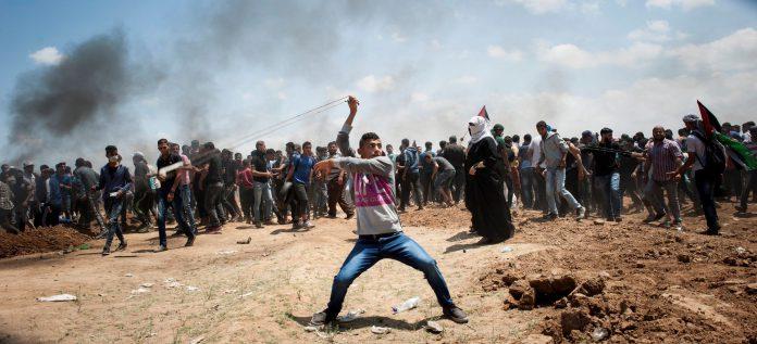 Varios manifestantes palestinos arrojan objetos a las fuerzas de seguridad de Israel en medio de las protestas que han sacudido la frontera en Gaza.