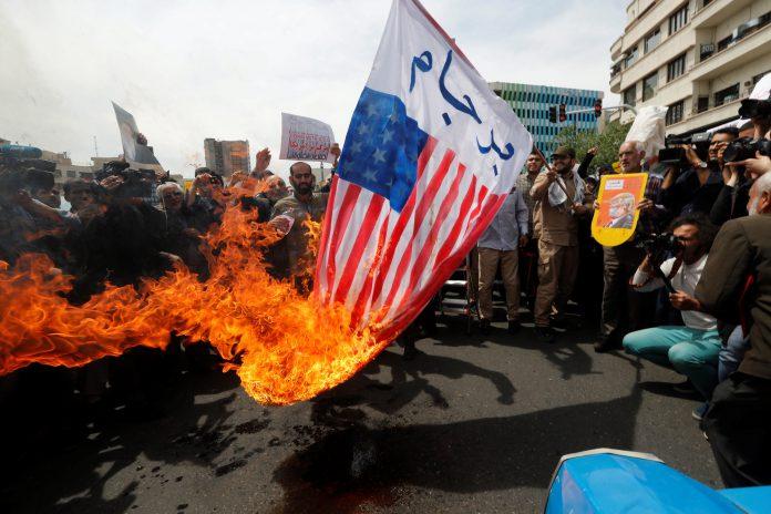 Iraníes queman banderas estadounidenses durante una manifestación contra Estados Unidos tras la oración de ayer.