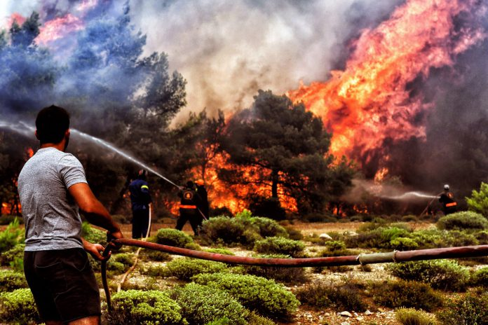 Bomberos y voluntarios luchan contra las llamas en un incendio en Verori, cerca de Loutraki.