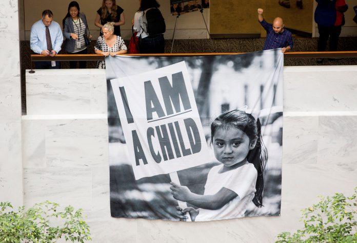 Varias personas participan en una sentada para demandar a la administración Trump la reunificación de las familias.