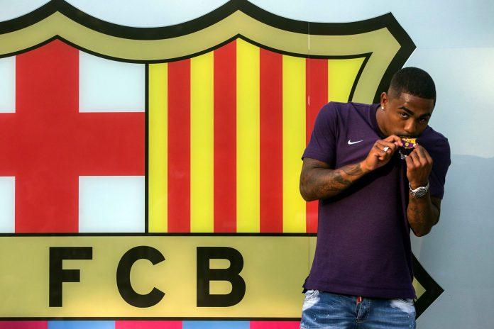 El atacante brasileño Malcom besa el escudo del Barça al llegar a las oficinas del conjunto azulgrana.