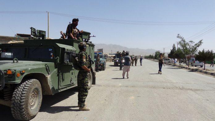 Oficiales de seguridad montan guardia en las carreteras que conducen al escenario del ataque en Afganistán.