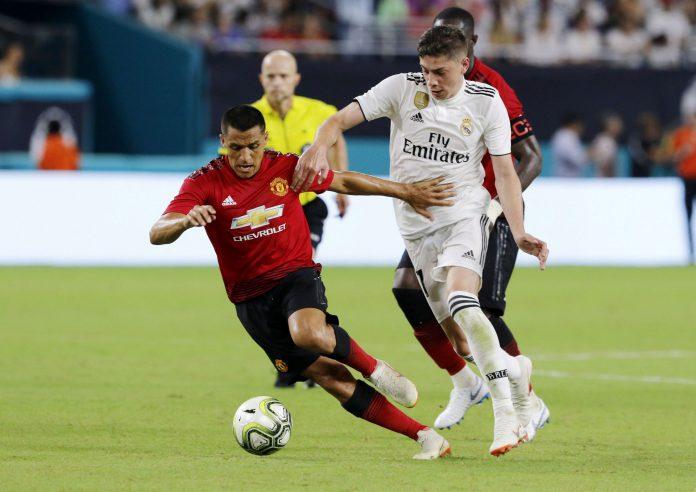 El madridista Federico Valverde intenta atajar al delantero del Manchester United Alexis Sánchez. / EFE