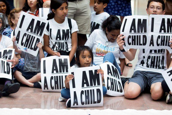 Niños participan en una sentada para demandar a la administración Trump la reunificación de las familias separadas.