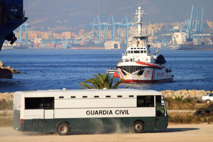 Un autobús de la Guardia Civil espera la llegada de los inmigrantes para su identificación.