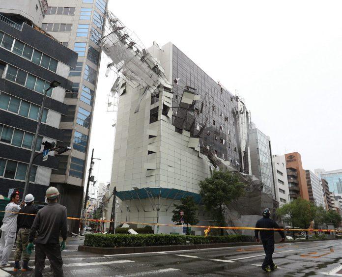 Varias personas observan el estado en el que quedó un edificio en la ciudad japonesa de Osaka.