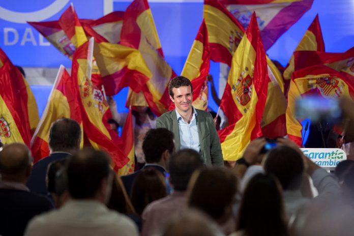 El presidente del PP, Pablo Casado, envuelto en banderas de España durante el acto organizado en Málaga con motivo de la Fiesta Nacional.