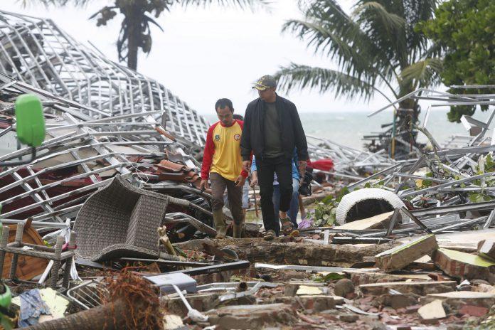 Dos hombres caminan entre los destrozos provocados por el tsunami en Pandeglang. Varias zonas turísticas del país se han visto seriamente afectadas.
