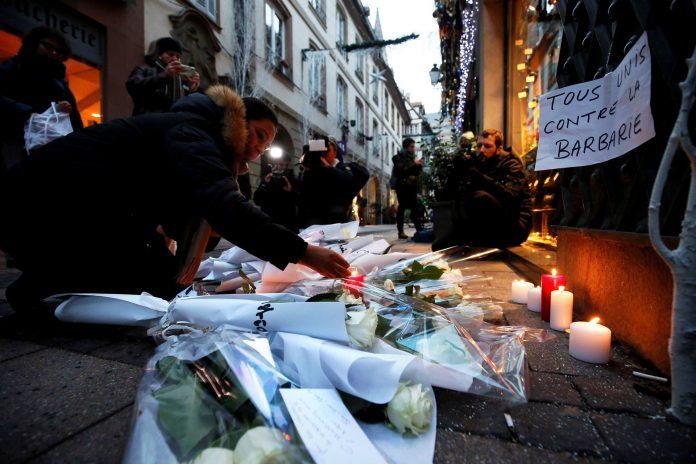 Ciudadanos encienden velas en el lugar donde falleció una de las víctimas del tiroteo de Estrasburgo.