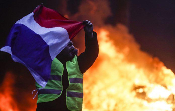 Un manifestante exhibe una bandera francesa ante uno de los muchos incendios provocados en los disturbios.