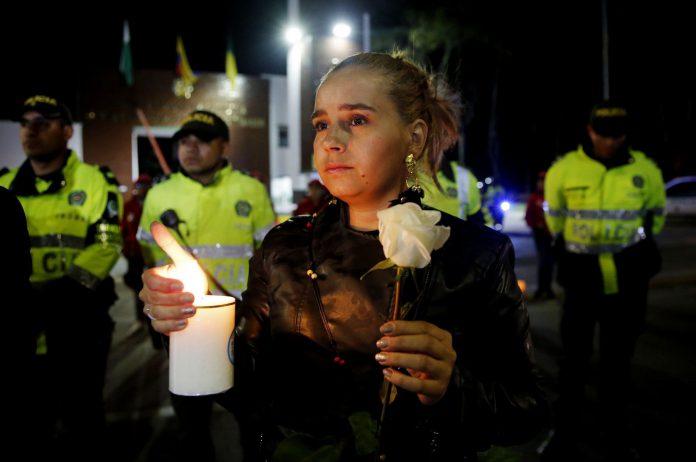 Ciudadanos y policías participan en un plantón frente a la Escuela de Policía donde murieron más de 20 personas.