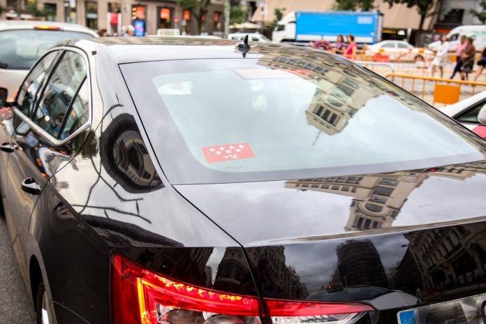 Un cohe con licencia VTC Uber o Cabify circula por Madrid.