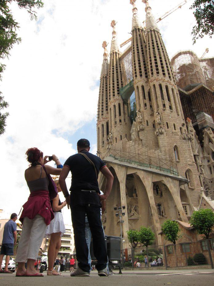 Un grupo de turistas fotografía la Sagrada Familia en Barcelona.