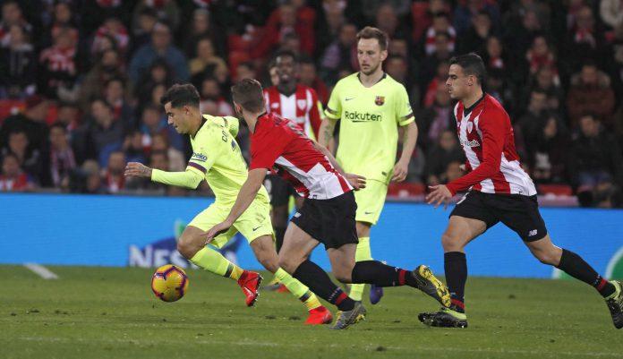 El centrocampista brasileño del Barcelona Philippe Coutinho (i), intenta zafarse de dos jugadores del Athletic Club en el partido de ayer en el estadio bilbaíno de San Mamés