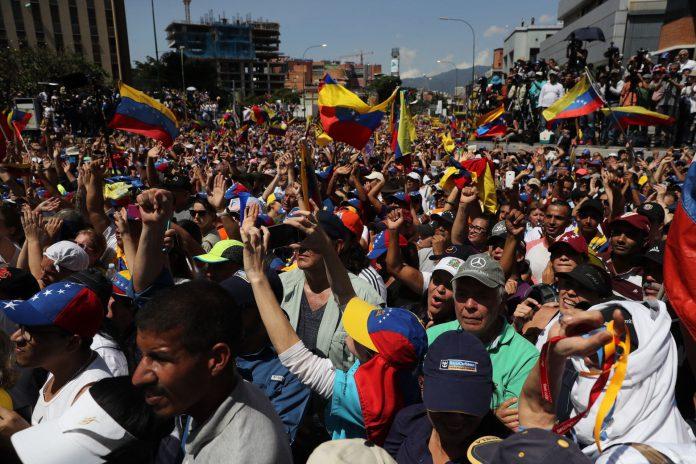 Opositores venezolanos escuchan el discurso de Juan Guaidó durante la marcha contra el presidente Maduro.