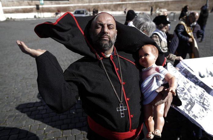 Un hombre vestido como un cardenal participa en la Marcha por la Tolerancia Cero, durante la reunión sobre la crisis mundial de abuso sexual en el Vaticano.