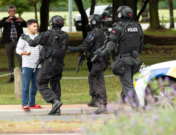 Agentes de policía hacen retroceder a varias personas de la escena del tiroteo en Cristchurch, Nueva Zelanda, que se ha saldado con 49 muertos.