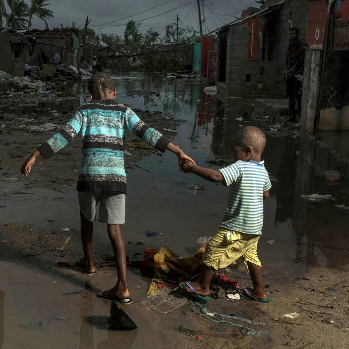 Dos niños cruzan una calle inundada en una población de Mozambique.