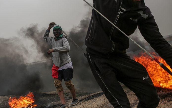 Varios manifestantes palestinos lanzan piedras contra posiciones israelíes.
