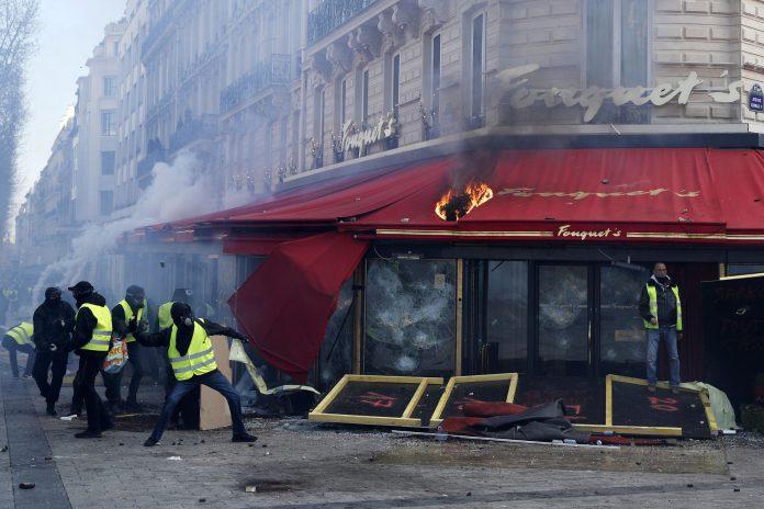 """Varios """"chalecos amarillos"""" se enfrentan contra la policía antidisturbios ante el restaurante Fouquet en París."""