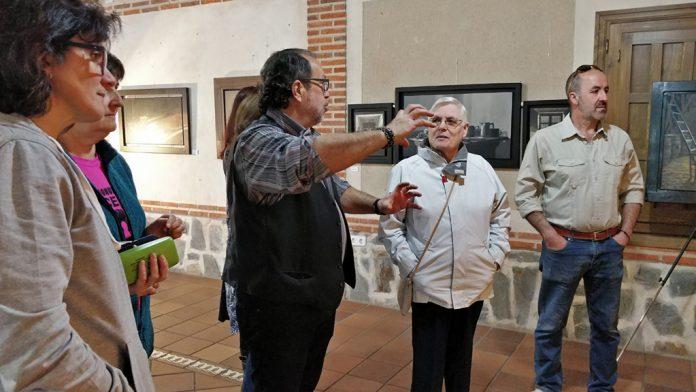 El pintor explica sus obras a los visitantes de la exposición.