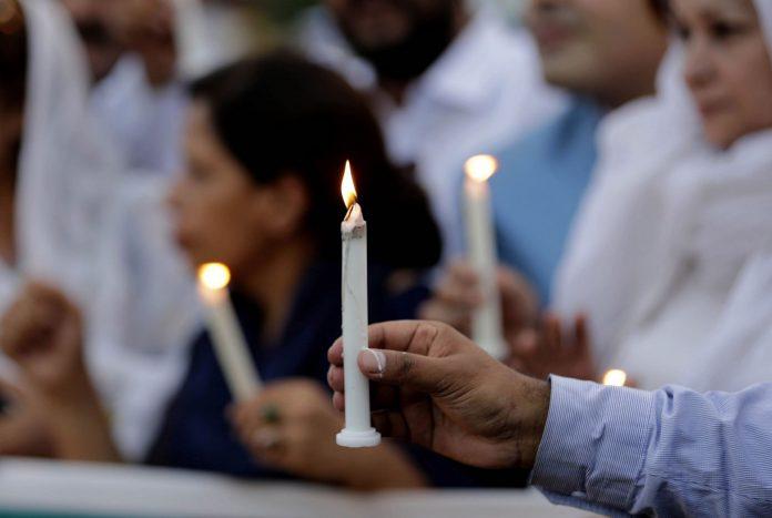 Varios activistas encienden velas en homenaje a las víctimas.