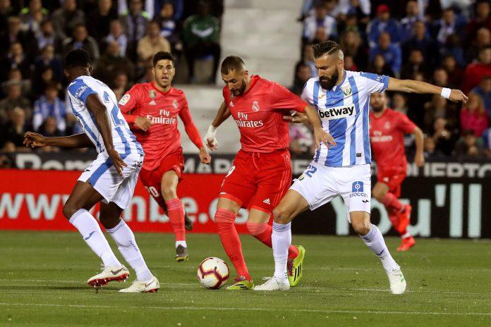 Benzema, autor del gol que rescataba un punto para el Real Madrid en Butarque, intenta superar la presión de la defensa del Leganés.
